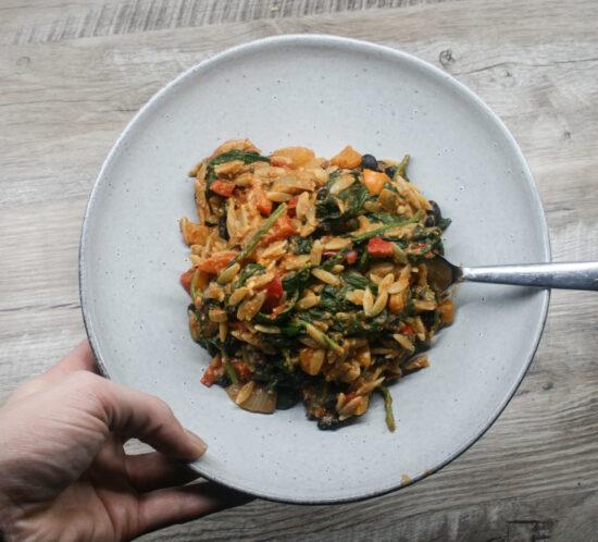 Orzo met zwarte bonen, geroosterde pepers en spinazie
